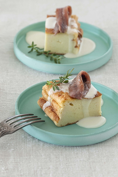 Potato cake with fondue and anchovies